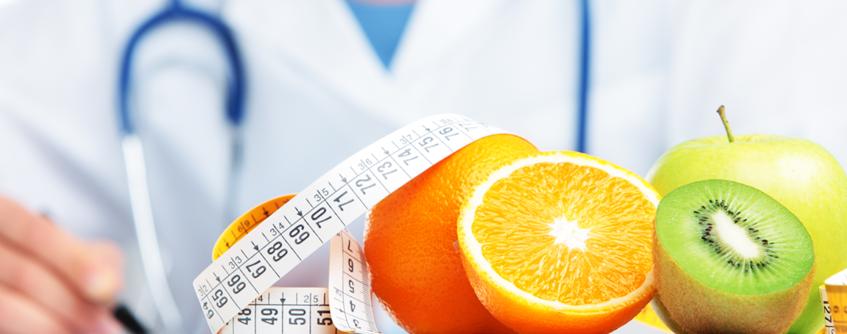 Nutricionista com frutas sobre a mesa do consultório
