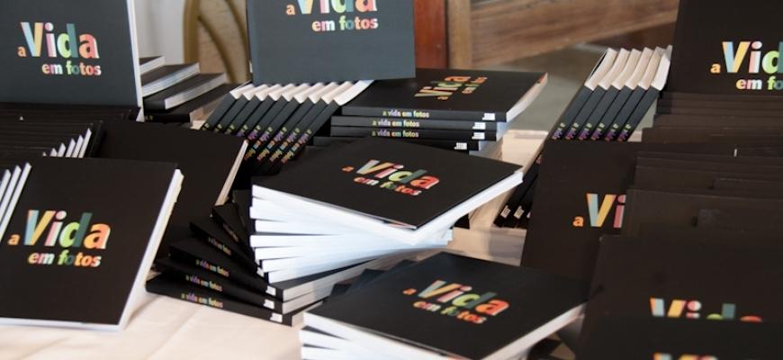 Foto da mesa de lançamento do Livro Vida em Fotos com diversos livros.
