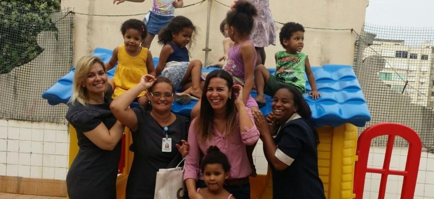 Funcionários e crianças brincando em uma casa de boneca